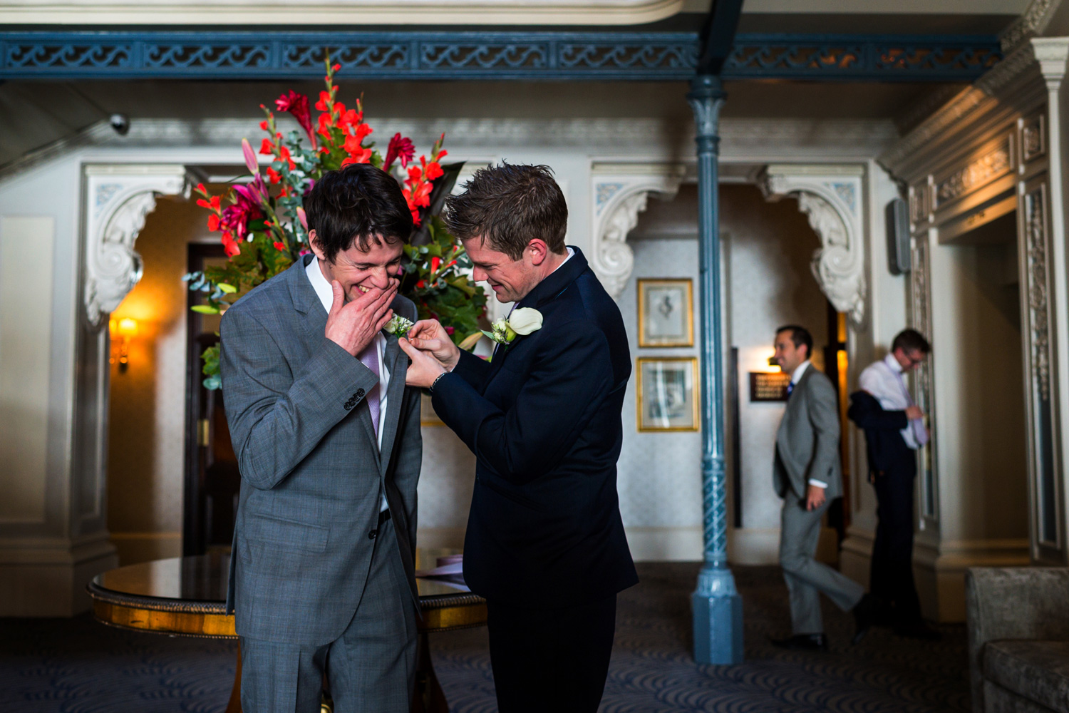 groom and best man putting on button hole