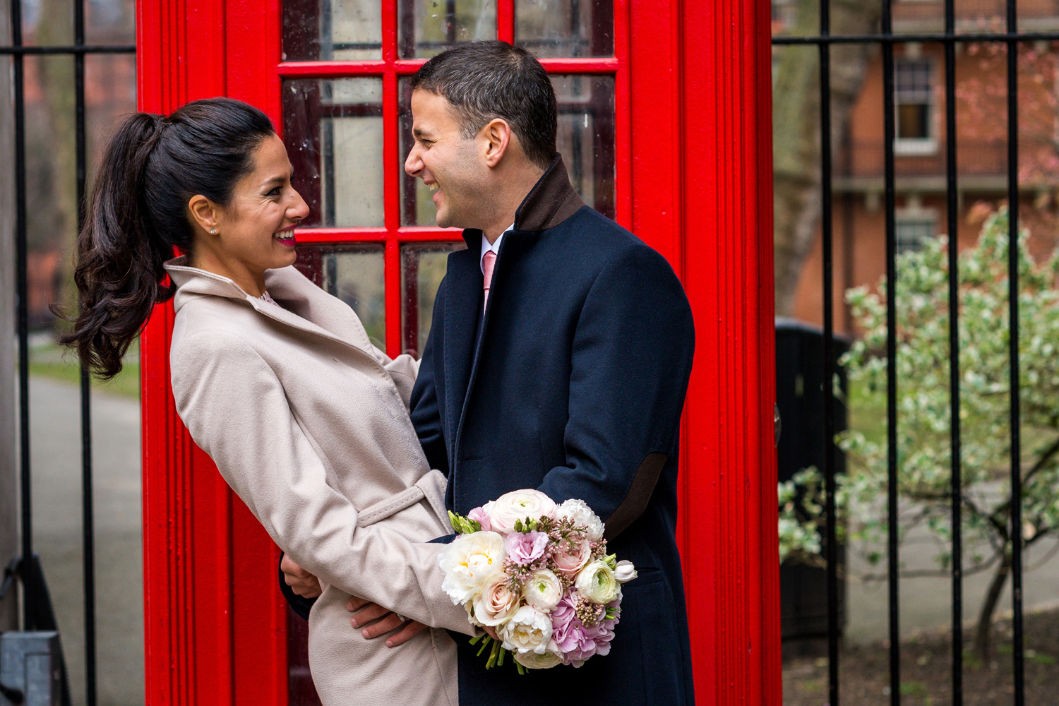 birde and groom in front of red phone box