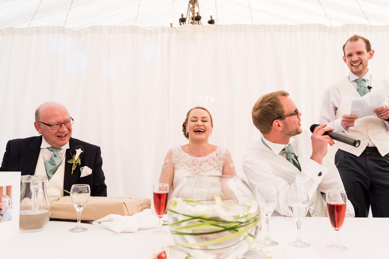 bride laughing during wedding speech