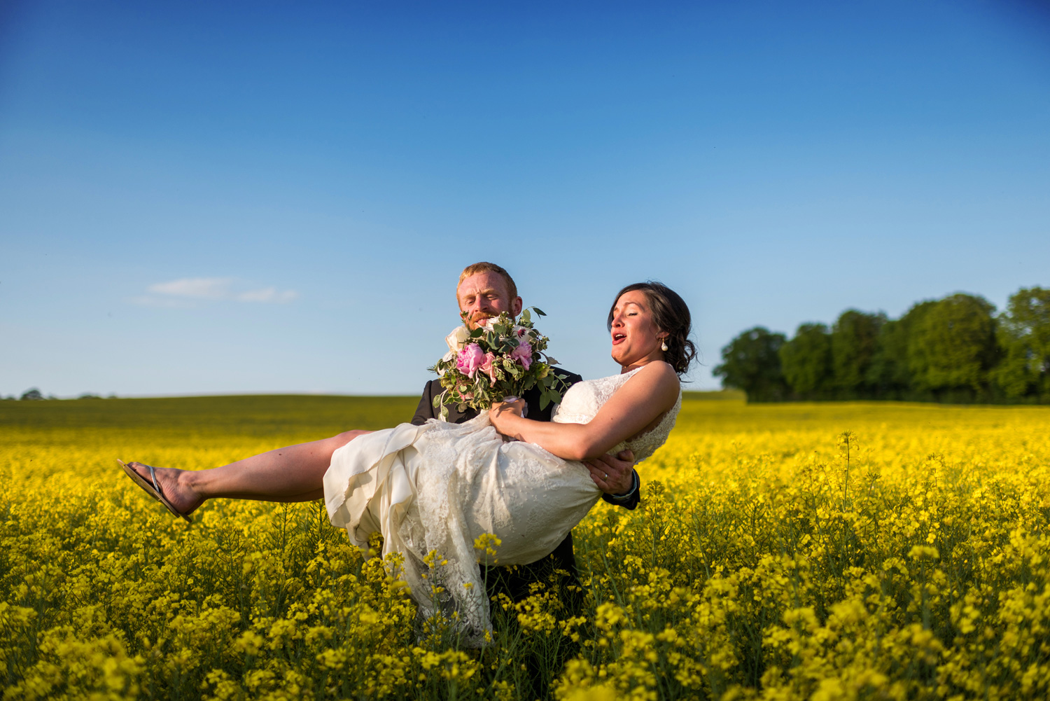 groom carrying bride out of field